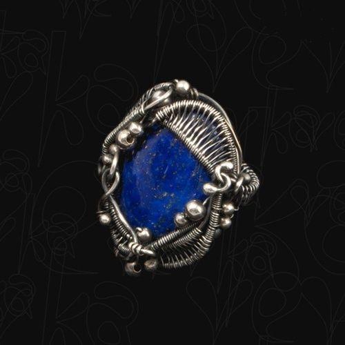 Oryginalny pierścień, którego sercem jest przepiękny, pochodzący z Indii kaboszon lapis lazuli. Kamień zamknęłam w misternej ramie wyplecionej z czystego srebra (próba 999). Wykonanie w całości ręczne z użyciem techniki wire wrapping. Ze względu na rozmiar korony, pierścień będzie najlepiej prezentował się na palcu środkowym lub wskazującym. Całość oksydowana i starannie wypolerowana.