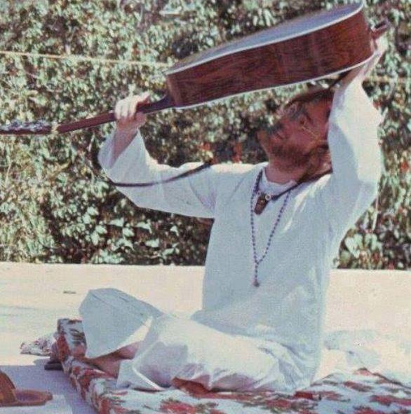John Lennon losing his guitar pick in his guitar, India, 1968.