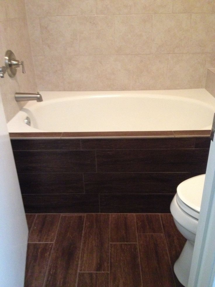 dark walnut wood tile floor and bathtub face contrast