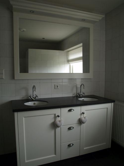 Landelijk badkamermeubel voorzien van een composiet stenen blad met twee ronde keramische onderbouwwastafels. Het meubel is hierbij gecombineerd met een spiegel in dezelfde stijl als het meubel en tevens voorzien van verlichting. De spiegel kan eveneens verwarmd worden zodat een radiator in de badkamer overbodig wordt en u daarmee ruimte kunt besparen. Het meubel is gerealiseerd door VRI interieur.