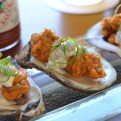 BBQ Oysters at New Orleans' Red Fish Grill are coated in cornmeal, flash fried, tossed with Crystal hot sauce and topped with a chunky, crumbly blue cheese dressing. (Photo Credit: Red Fish Grill)