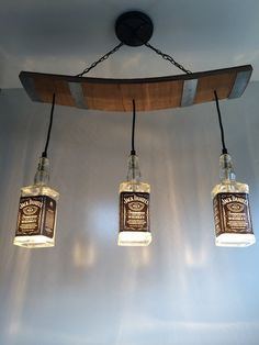 This light fixture is made from repurposed Jack Daniels bottles and wooden slats from a used barrel including the metal bands. Would be a