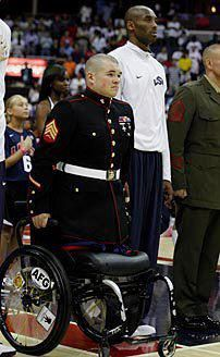 Sgt. Zachary Stinson, USMC, uses his arms to stand for the playing of the National Anthem. Words cannot explain how inspiring this is.