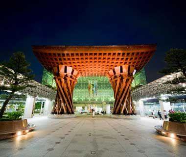The entrance to the impressive Kanazawa train station in Kanazawa, Japan. The massive stylized torii dwarfs everything around it. mikecranephotography.com / Alamy