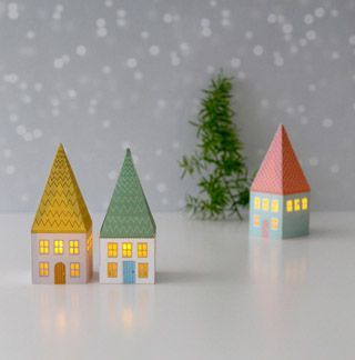Another fun & free printable paper craft! A set of mini paper houses glowing with LED candle lights! Make a Christmas village or use as ornaments!