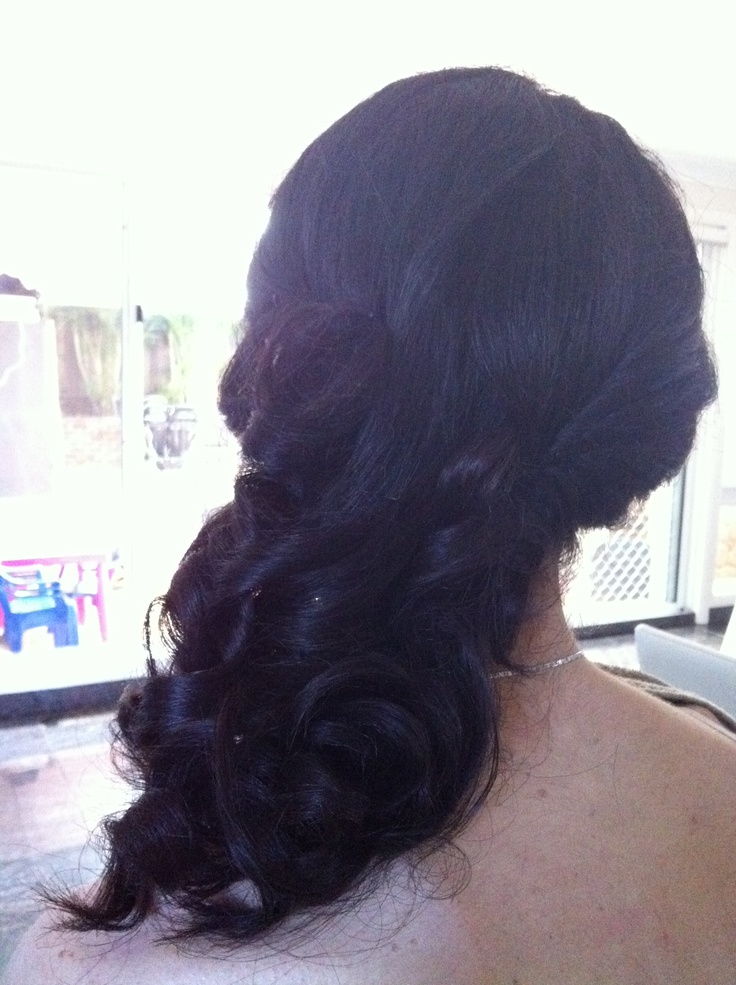 Soft ghd curls all pinned to the side.