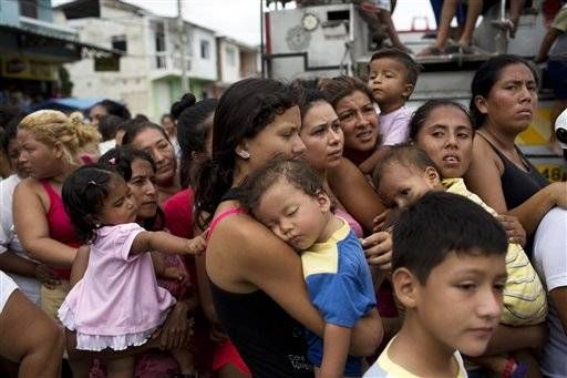 Women and children wait in a line for over an hour for free food and water from the government, days after an earthquake in Crucita, Ecuador, Thursday, April 21, 2016. The damage from the 7.8-magnitude quake adds to already heavy economic hardships being felt in this OPEC nation triggered by the collapse in world oil prices.