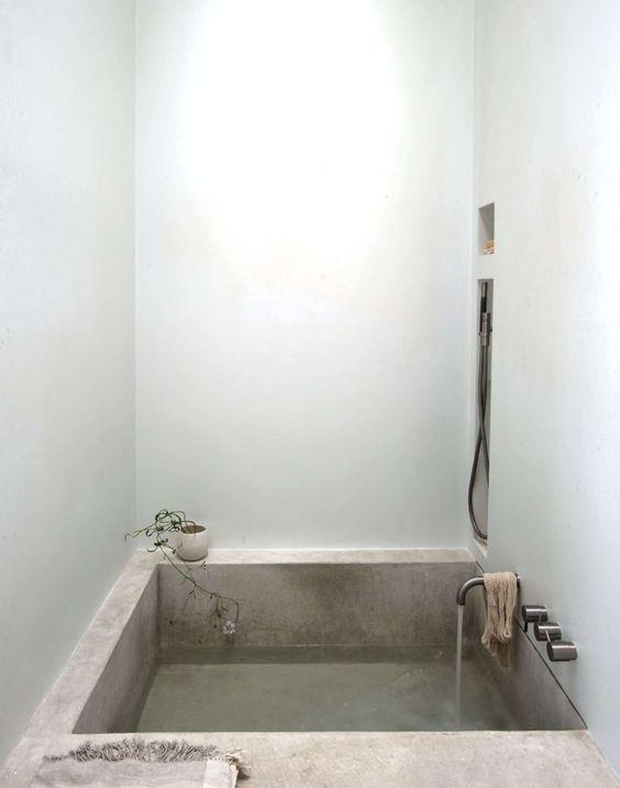 Квадратная бетонная ванная создает ощущение спа в небольшом помещении. .