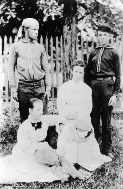 About eighteen years old Theodore Roosevelt (top left) with brother Elliott, sister Corinne and family friend Edith (who would later become his second wife). The look of the eyes and the brow are the same, but the body of TR here, around 1876, is now much stronger, the product of a home gym his father had created for him.