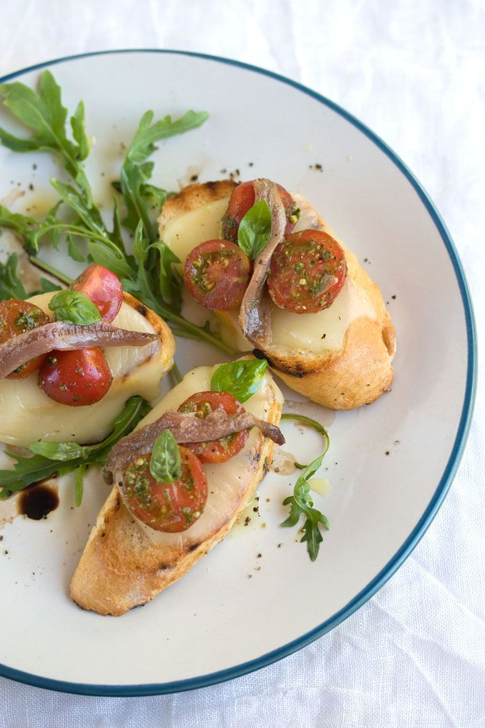 mozzarella toasts with basil, tomatoes and anchovies