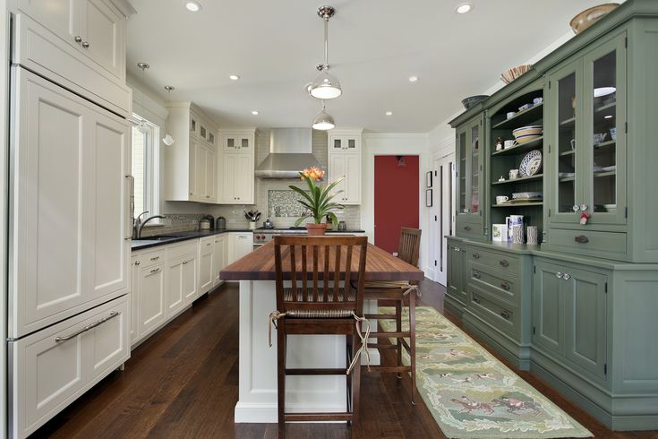 Kitchen design with white and green cabinets.  Bright red door adds a splash of color.