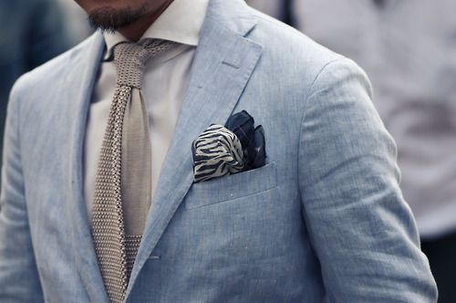 Casual and sophisticated. A knitted tie in sandy beige, light causal blazer in pale sky blue with a crumpled navy pocket square, all matched back with a simple white shirt.