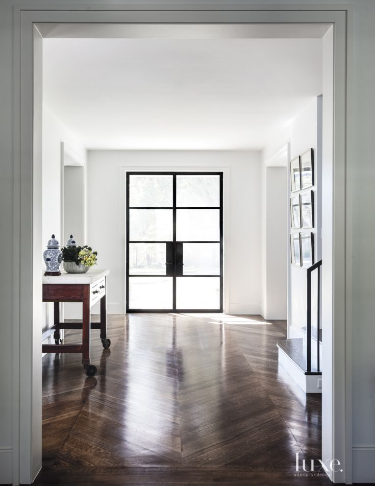 Santiago Iron Works fabricated the custom steel-framed entry door. Builder Ben Coats specified a herringbone pattern for the floor for interest and architect Paul Turney moved the staircase toward the wall to keep the view through the house open.