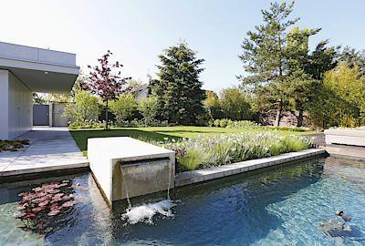 Okrasná vodní plocha v betonovém bazénku s přepadem vody jako součást menší zahrady umožňuje osvěžení končetin. Leknínům na vodní hladině to nevadí.
