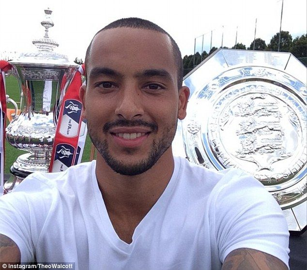 Selfie: Theo Walcott enjoys the winning feeling as he smiles with the FA Cup and Community...