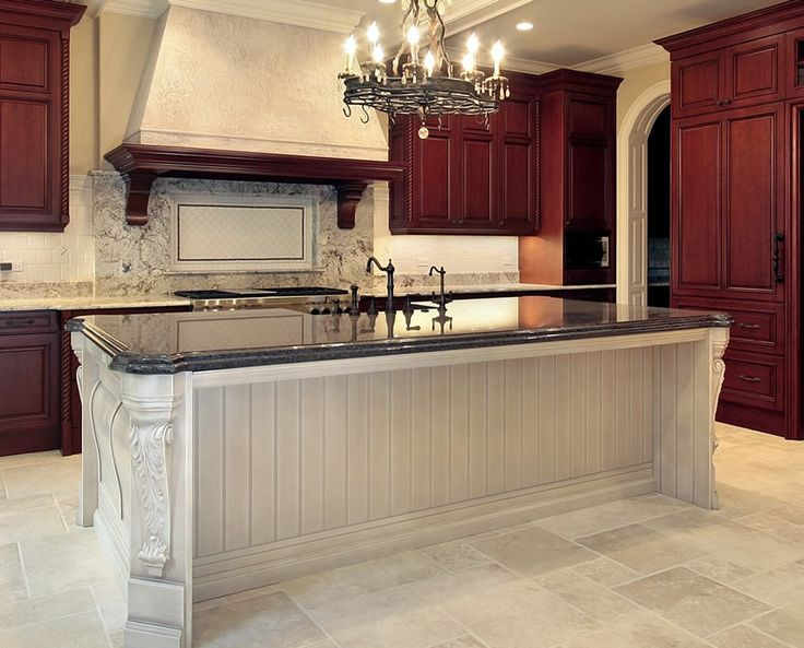 Gorgeous custom kitchen island with ornate wood carving in the cabinet and a blue azure granite counter.