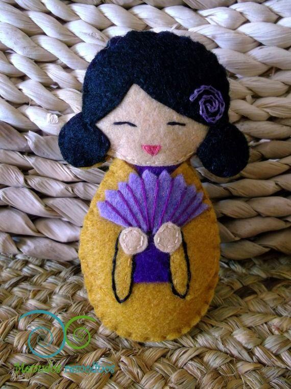 Broche realizado en fieltro para utilizarlo prendido en la ropa, bolso, mochila, etc.El motivo es una muñeca japonesa Kokeshi en tonos mostaza con ab