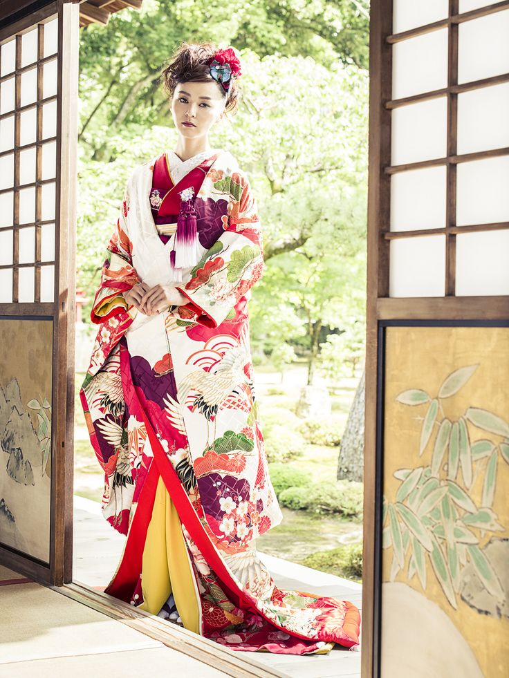 色打掛(Iro Uchikake)/おめでたい兆しの象徴である瑞雲とは五色の色彩を放つ吉祥の証。優美で美しい鶴がまるで、未来に進むお二人を祝福しているかのように舞羽ばたきます。桧垣に本紋の柄ゆきのつややかで美しい上質の生地を用いて染め上げ、一面に職人の手作業により金駒刺繍を施しました。アンティーク着物のような色彩が大変趣のある御婚礼衣裳です。