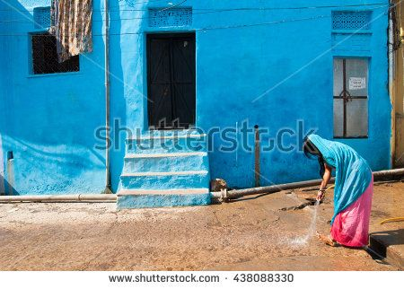 "Bundi, Rajasthan, India. November 30, 2010. Unidentified woman cleans the area outside his home. Street scene. ""Blue City"" Bundi, Rajasthan, India - stock photo"