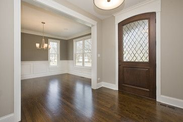 "Oak floors. Stain is Minwax Dark Walnut. Trim is BM Dove White.   Benjamin Moore 984 ""Stone Hearth""- Foyer   Benjamin Moore 1475 ""Graystone""- Dining Room"