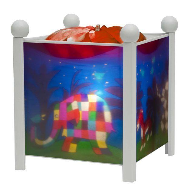 """La """"lanterne magique"""" Elmerest une veilleuse traditionnelle qui accompagne les enfants dans leur sommeil en les apaisant au moment de s'endormir. Dès qu'on l'allume, la chaleur de l'ampoule (12V - 20W) actionne une hélice qui fait tourner le décor : une"""