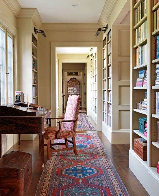 A writing desk sits before a window in this book-lined, paneled hallway with lovely traditional design details - Traditional Home®  Photo: Jonny Valiant and Joseph St. Pierre Design: Nancy Gould