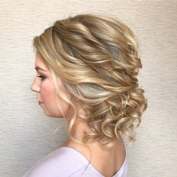 A Messy Twisted Low Updo With Curls And Bangs Is A Very