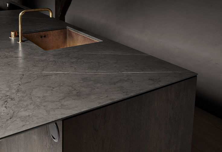 To intensify the striking effect of the marble counter, we have inserted a brass sink and coupled it with a Vola faucet.