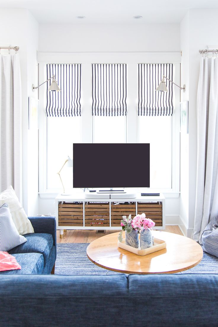 www.pencilshavingsstudio.com  Bright white living room with custom Sunbrella Lido stripe roman shades by Loom Decor. Swing arm library sconce in nickel by Restoration Hardware. IKEA hack media cabinet and custom coffee table with hairpin legs. See the whole room at pencilshavingsstudio.com