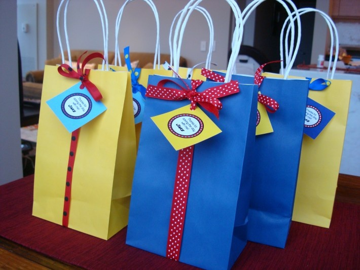 Love the blue and yellow bags for the party favors! The ribbon and favor tags are so cute for this superhero themed birthday party