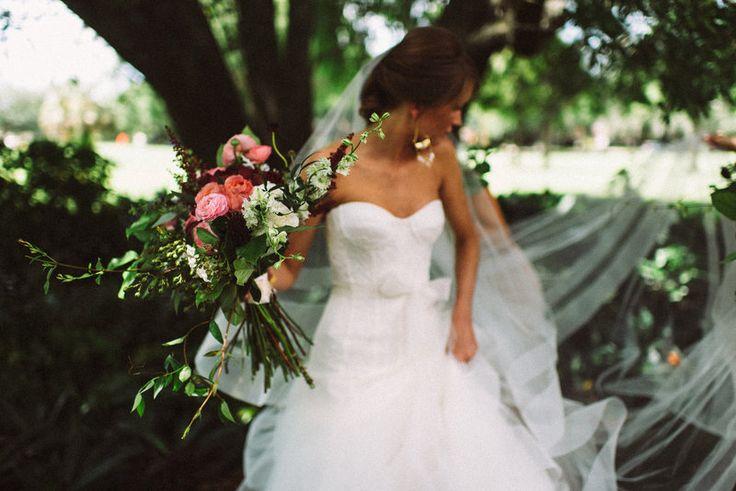 heading to her wedding, the bride clutches her lush summer bouquet of pink garden roses,  burgundy scabiosa,burgundy astilbe, red peonies, pink ranunculus, white larkspur, white spray roses, jasmine vine, crepe myrtle, fern and lemon leaf.