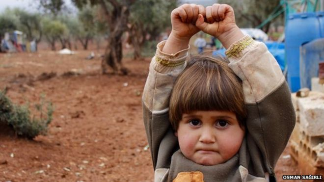 """Syria. Hudea, a four-year-old girl with her hands up in surrender by Turkish photographer Osman Sağırlı.The image was taken at the Atmeh refugee camp in Syria, in December 2014. She travelled to the camp - near the Turkish border - with her mother and two siblings. It is some 150 km from their home in Hama. """"I was using a telephoto lens, and she thought it was a weapon,"""" says Sağırlı. """"İ realised she was terrified after I took it, and looked at the picture, because she bit her lips and…"""