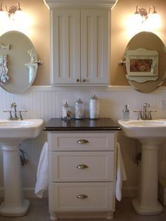 Two pedestal sinks separated by a storage unit and counter, rather than a double vanity. Interesting idea!