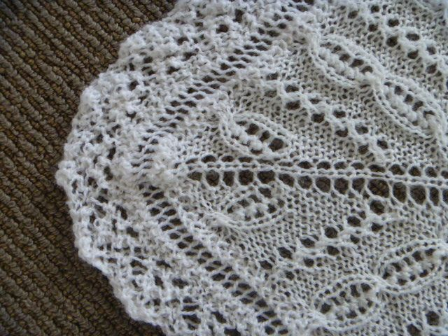 2ply baby shawl mitred corner with lace edging.  The edging is added last with straight needles picking up and decreasing off as you go.  The lace edging is approx 12 stitches wide with increasing and decreasing for the scalloped edging.