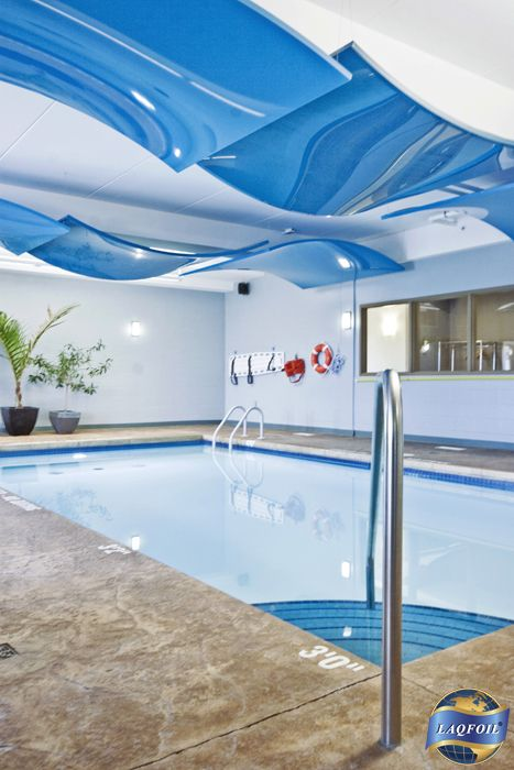 Design: ACI Wright Architects, Inc. Best Western Hotel, Walkerton ON, Canada Curved high gloss panels wrapped with Laqfoil stretch ceiling attenuate noise and hide pipes with an artistic suggestion of waves. Stretch ceilings are perfect in swimming pool rooms! Unaffected by high humidity, they block the spread of chlorine fumes, they never need to be repainted, they cut down on unwanted noise, and for those who swim or float on their backs, the ceiling is the main view! www.laqfoil.com
