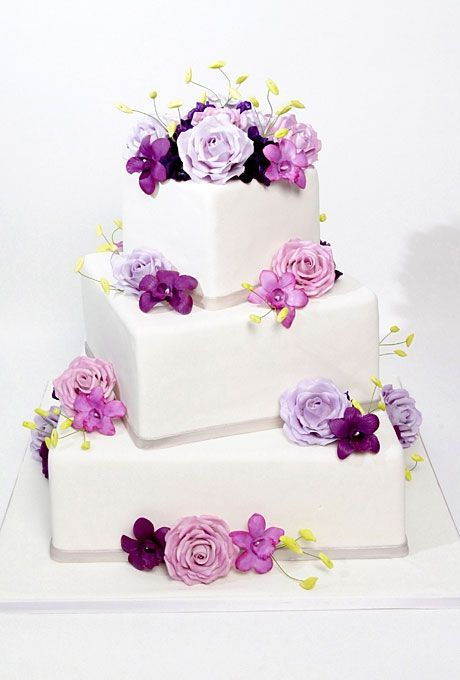 White fondant wedding cake with square tiers decorated with pink and purple roses and orchids.