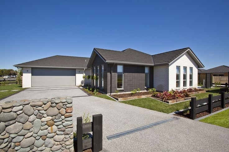 Natural elements including a stone wall and wooden sleepers in the driveway, hint at the beach resort theme. A combination of Monier Bricks Vogue 'Arctic White' and Stackbonded Presto 'Skipjack' dyed with Nawkaw 'Nawtint', are used to create a modern brick look on the outside of this home.