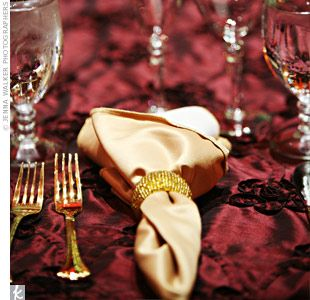 Gold rimmed glasses and dinnerware gave the place settings a touch of old-world Tuscany. Rich burgundy linens topped the tables for a strong contrast against the gold napkins and beaded napkin rings.
