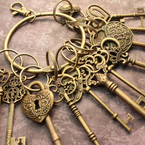 A large ring supporting 12 large antique brass keys with unique designs. Perfect for decoration or to separate the items for creations. This set