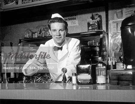 1950s SMILING YOUNG MAN SODA JERK LEANS ACROSS COUNTER OFFERING AN ...