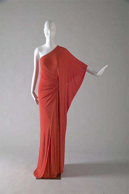 Red silk jersey evening gown by Halston, American, c. 1976. Born in Des Moines, Iowa, Roy Halston Frowick came to Chicago to attend the School of the Art Institute. He opened a millinery studio in the early 1950s and later moved to New York to launch his dressmaking career. Halston soon became known for his classical designs in silk jersey and Ultrasuede.