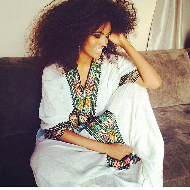 Ethiopian woman in beautiful white dress with traditional embroidered trim.