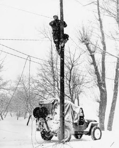 A Signal Corps lineman repairs damaged telephone lines, Belgium, winter 1944-1945. The jeep is equipped with a RL-31 wire reel carrier.