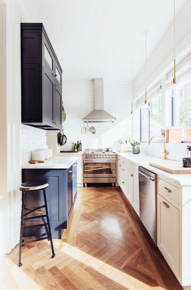 This galley kitchen combines contrasting cabinets, herringbone wood flooring, and a subway tile backsplash to create a modern look. Take inspiration from this space for your next home renovation.