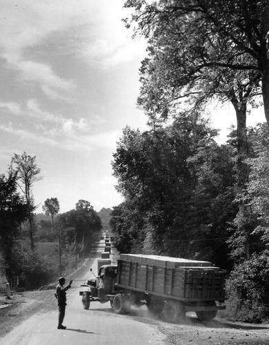 La police militaire dirige un convoi sur la Red Ball Express en Normandie.