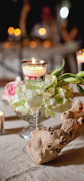 silver or gold rimmed champagne flute with floating candle, and hydrangea, tulips, and spray roses in a vintage glass compote. Grapevine wood on table.