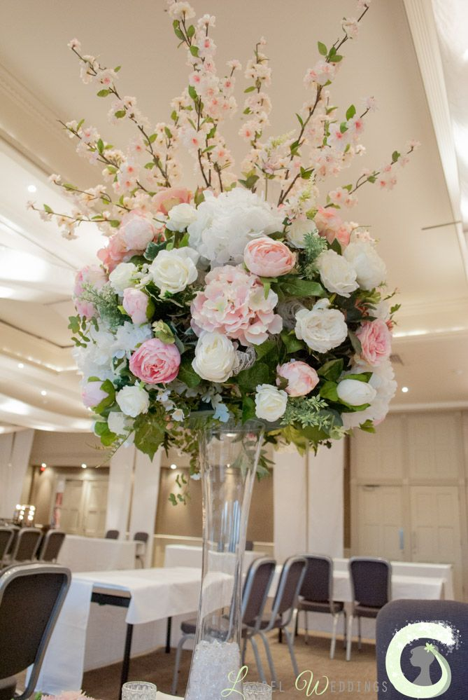 Tall vase centrepiece of pink and white silk flowers - The Mere wedding fayre spring 2016 @themereresort - Laurel Weddings http://www.laurelweddings.com/arrangements-from-the-mere-wedding-fayre/