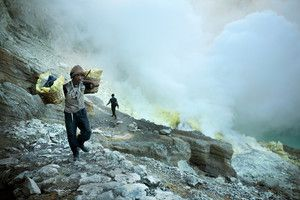 Sulfur-miner-walks-through-rough-terrain.jpg-The men depend on nothing more than a metal rod and sheer muscle power. They have no special equipment to assist them with the mining and little to no protection from the poisonous fumes that the volcano constantly expels. The job of the men at Kawah Ijen might be one of the most difficult and dangerous in the world.