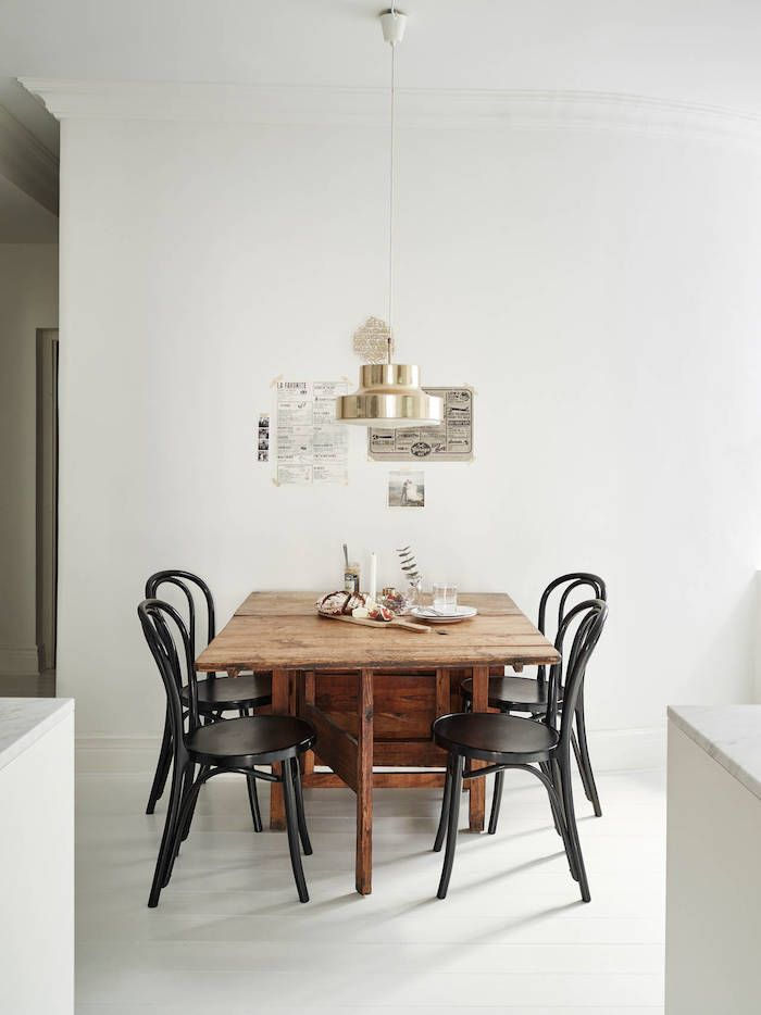 Vintage table, black Thonet chairs and brass Bumling light