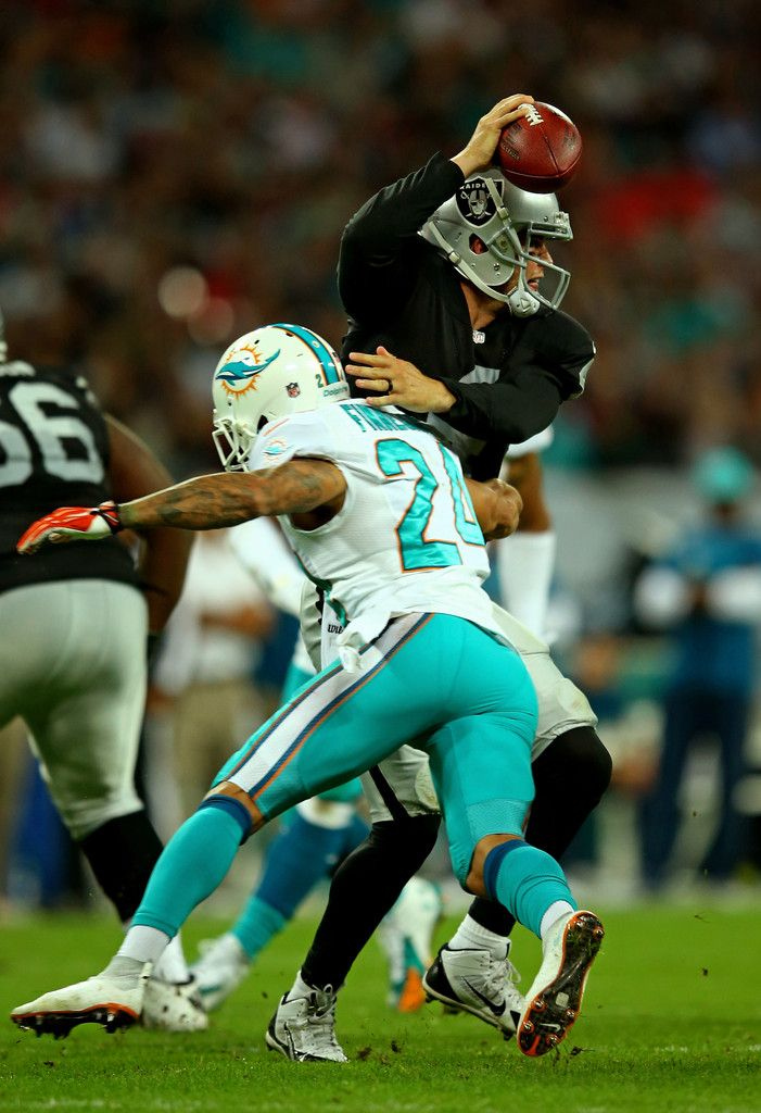 Cortland Finnegan #24 of the Miami Dolphins attempts to sack quarterback Derek Carr #4 of the Oakland Raiders during the NFL match between the Oakland Raiders and the Miami Dolphins at Wembley Stadium on September 28, 2014 in London, England.